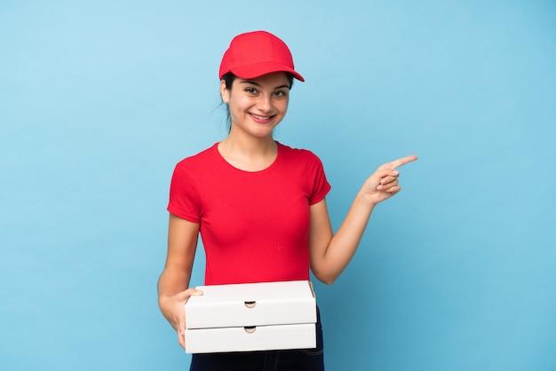 Mujer joven que sostiene una pizza sobre el dedo acusador de la pared rosada aislada al lado