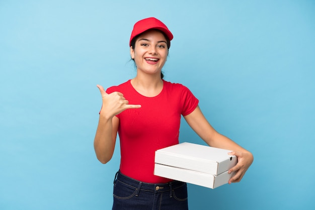 Mujer joven que sostiene una pizza sobre la pared rosada aislada que hace gesto del teléfono