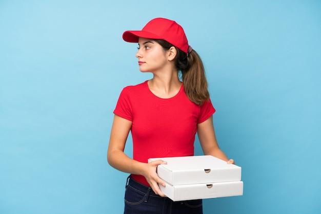 Mujer joven que sostiene una pizza sobre la pared rosada aislada que mira el lado
