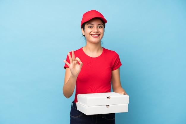 Mujer joven que sostiene una pizza sobre la pared rosada aislada que muestra una muestra aceptable con los dedos