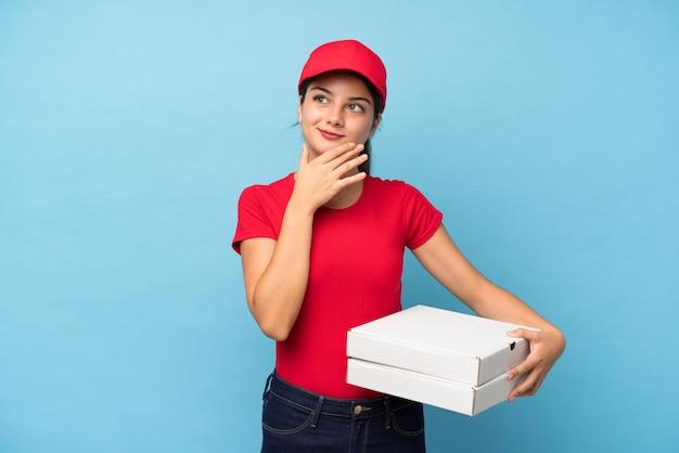 Mujer joven que sostiene una pizza sobre la pared rosada aislada que piensa una idea