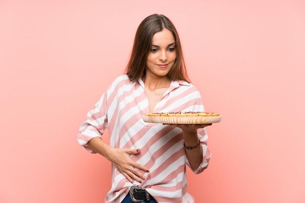 Mujer joven que sostiene una pizza sobre la pared rosada aislada