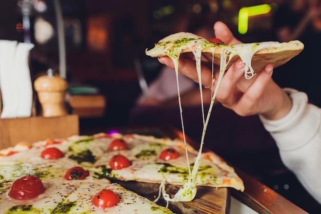 Mujer joven que sostiene la placa con la pizza sabrosa, visión ascendente cercana.