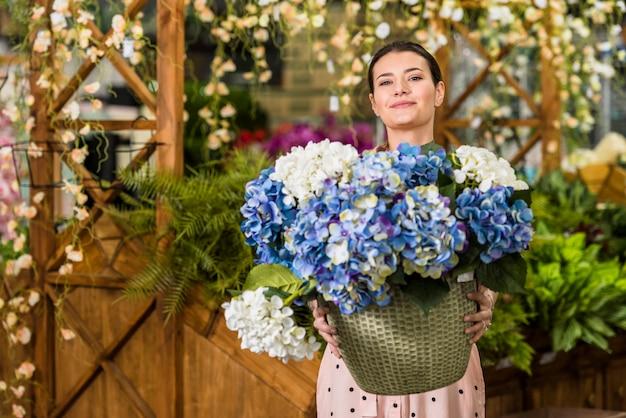 Mujer joven que sostiene el pote con las flores en casa verde