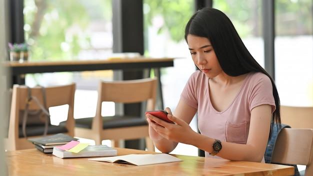 Mujer joven que sostiene smartphone en sala de biblioteca.