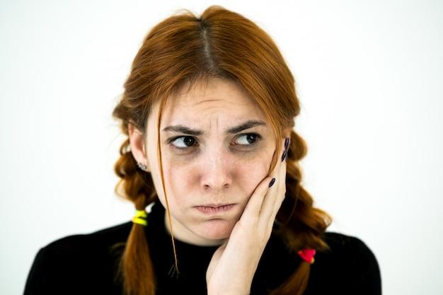 Mujer joven que sostiene su mano a la mejilla que tiene dolor de muelas.