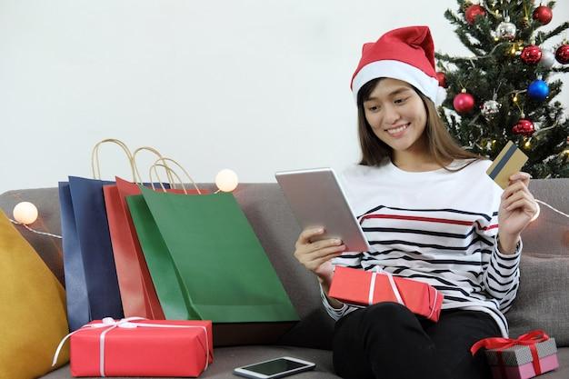 Mujer joven que sostiene la tableta digital y la tarjeta de crédito con muchos bolsos de compras y de la caja de regalo de la navidad.