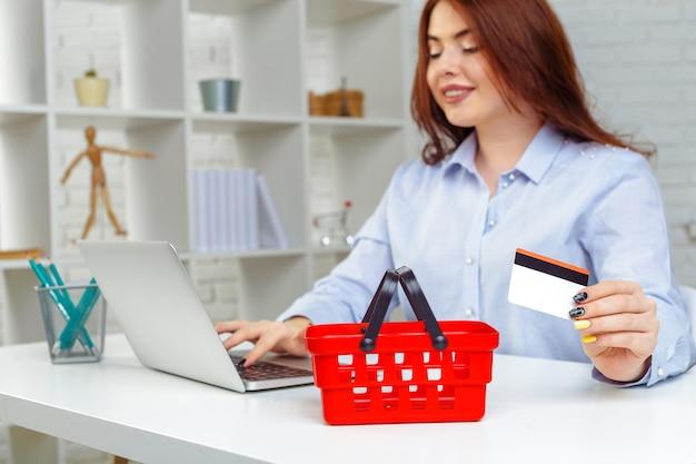 Mujer joven que sostiene la tarjeta de crédito y que usa la computadora portátil. concepto de compra en línea
