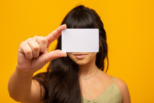 Mujer joven que sostiene la tarjeta de visita blanca en blanco