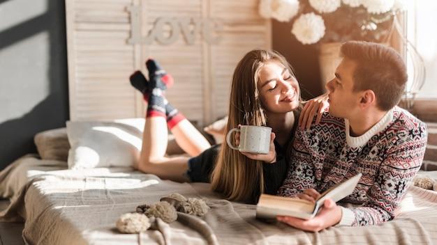 Mujer joven que sostiene la taza de café en la mano que mira al hombre que miente en cama