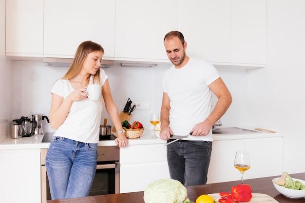 Mujer joven que sostiene la taza de café en la mano que mira a su marido que afila el cuchillo