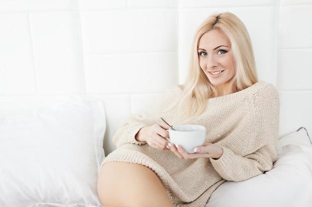 Mujer joven que sostiene la taza de café.