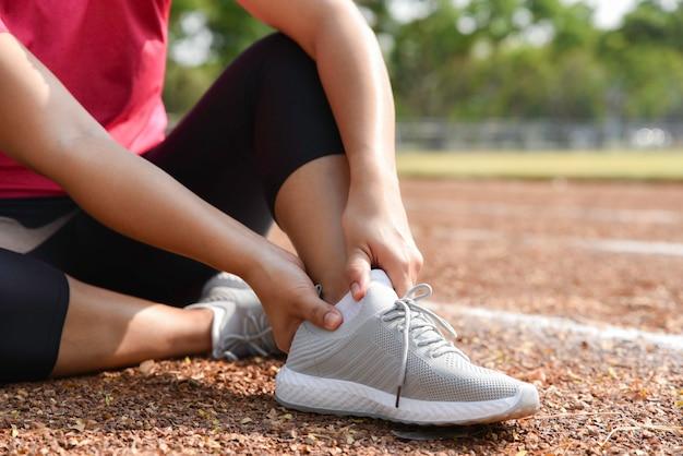 Mujer joven que sostiene el tobillo en dolor en la pista del estadio. articulación torcida rota corriendo lesión deportiva.
