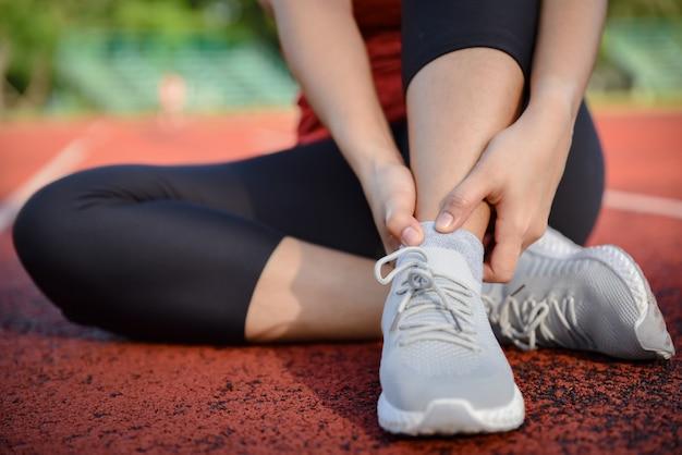 Mujer joven que sostiene el tobillo en dolor en la pista del estadio.