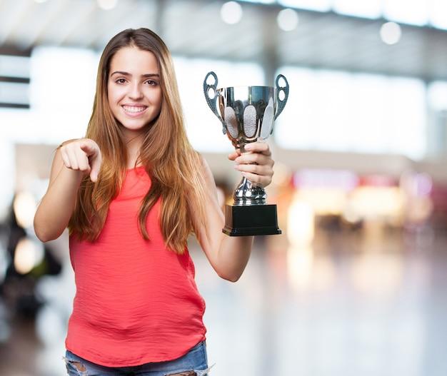 Mujer joven que sostiene un trofeo en un fondo blanco