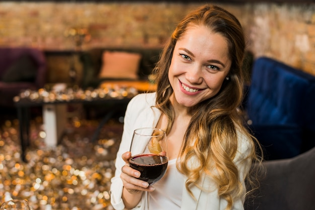 Mujer joven que sostiene un vidrio de vino rojo en barra