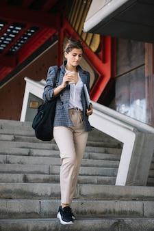 Mujer joven que sube y baja la escalera que sostiene la taza de café disponible y la tableta digital