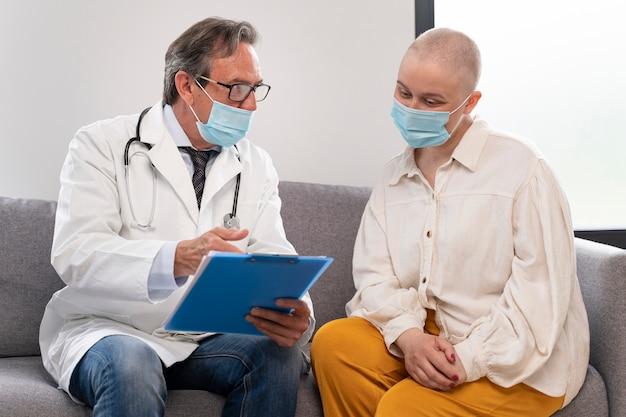 Mujer joven que sufre de cáncer de mama hablando con su médico