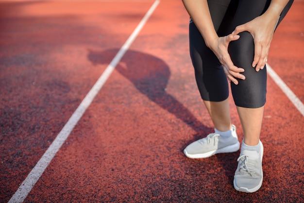 Mujer joven que sufre de correr la rodilla o lesión en la rótula