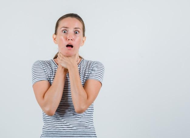 Mujer joven que sufre de dolor de garganta en camiseta a rayas y parece enferma. vista frontal.