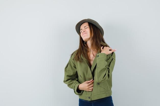 Mujer joven que sufre de dolor en el hombro en chaqueta, pantalón, sombrero y aspecto cansado, vista frontal.