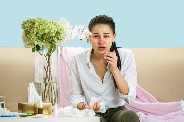 Mujer joven que sufre de polvo doméstico o alergia estacional. estornudar en la servilleta y sentarse rodeado de servilletas usadas en el suelo y el sofá. tomando medicamentos sin resultado. concepto de salud.