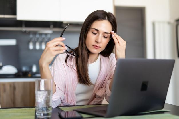 Mujer joven que tiene dolor de cabeza mientras trabaja en la computadora portátil que se sienta en su mesa de cocina en casa.