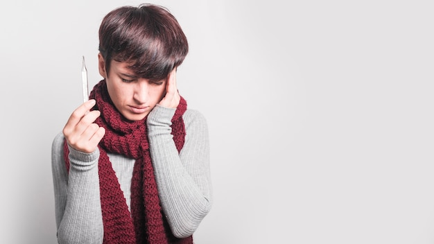 Mujer joven que tiene dolor de cabeza que sostiene el termómetro contra fondo gris