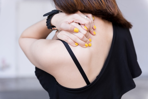 Mujer joven que tiene un dolor de cuello