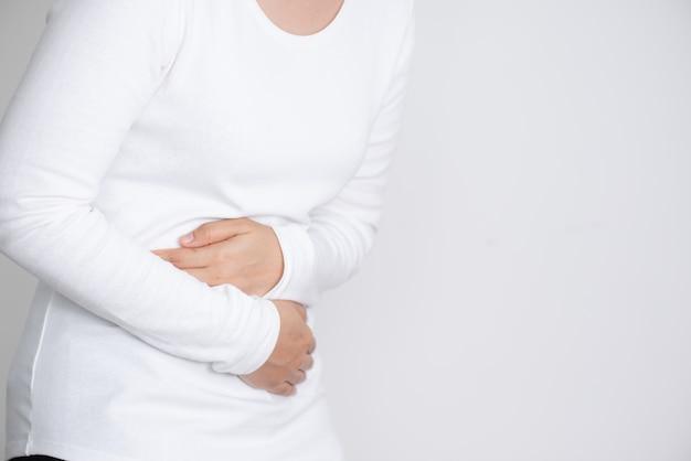 Mujer joven que tiene dolor de estómago doloroso