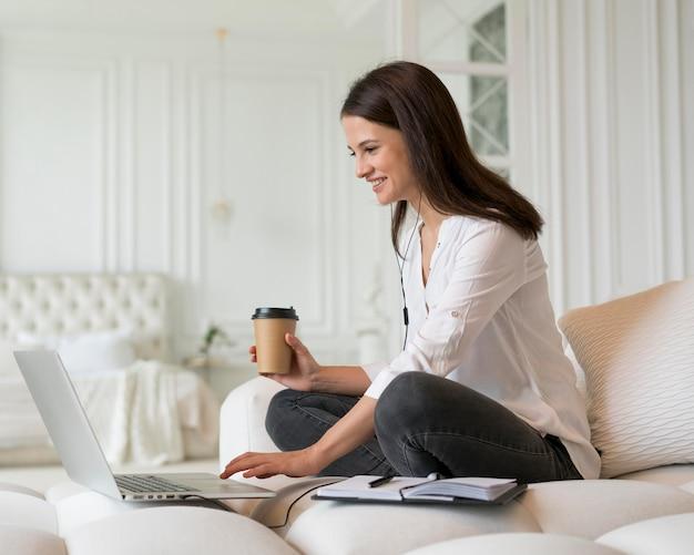 Mujer joven que tiene una reunión de negocios en línea en su computadora portátil
