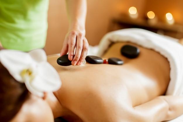 Mujer joven que tiene una terapia de masaje con piedras calientes
