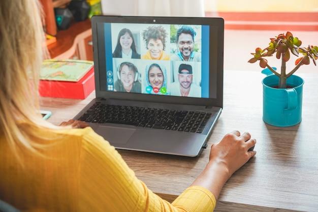Mujer joven que tiene una videollamada con amigos multirraciales durante la cuarentena de aislamiento