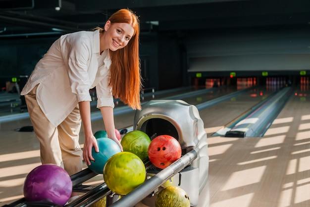 Mujer joven que toma una bola de boliche colorida