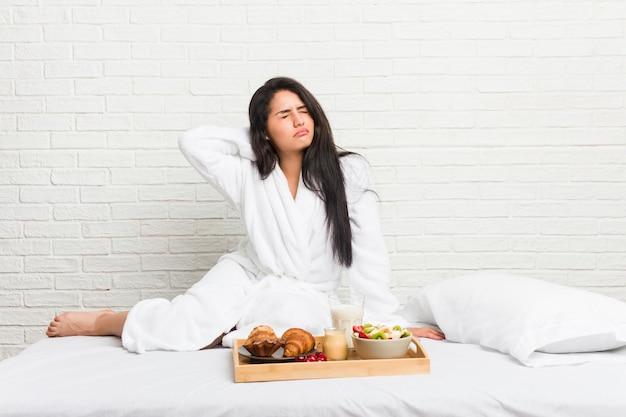 Mujer joven que toma un desayuno en la cama sufriendo dolor de cuello debido al estilo de vida sedentario.