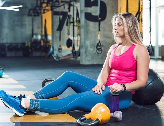 Mujer joven que toma descanso después del entrenamiento en gimnasio