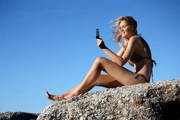 Mujer joven que toma una foto con el teléfono móvil en una roca del mar