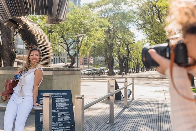 Mujer joven que toma la fotografía de su amiga posando en el parque