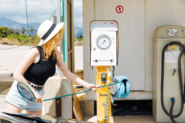 Mujer joven que toma la herramienta para llenar los neumáticos de coche con aire