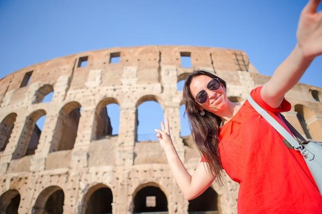 Mujer joven que toma el retrato del selfie delante del coliseo en roma, italia. niña feliz de vacaciones