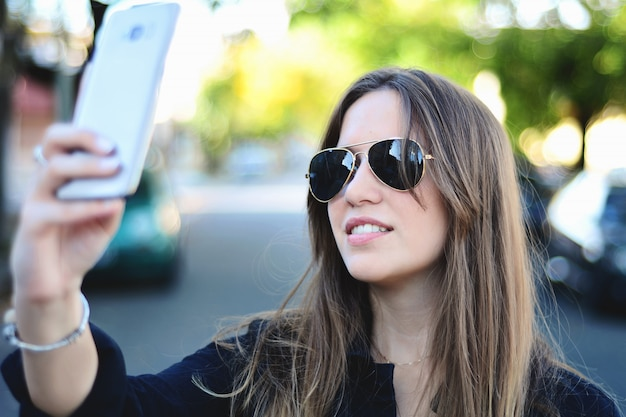 Mujer joven que toma selfie con su teléfono inteligente.