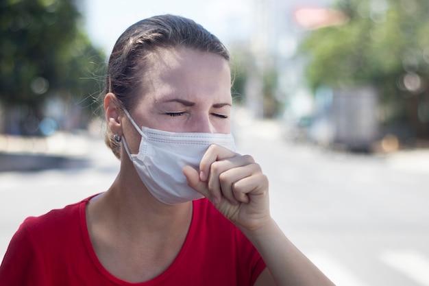Mujer joven que tose en máscara médica en su cara. retrato de niña enferma enferma al aire libre, sufriendo de dolor con los ojos cerrados. coronavirus, covid-19, concepto epidémico. síntomas del virus