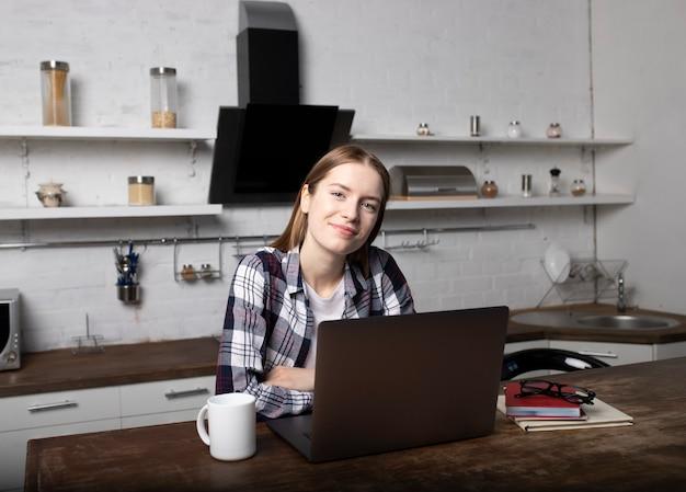 Mujer joven que trabaja en casa por la mañana. chica tomando café. ella esta usando su laptop