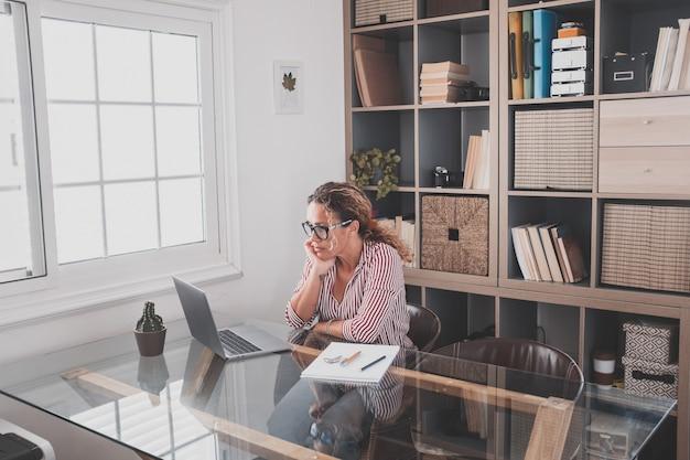 Una mujer joven que trabaja en casa en la oficina con una computadora portátil y un cuaderno tomando notas hablando en una videoconferencia. una mujer de negocios llamando a comunicarse