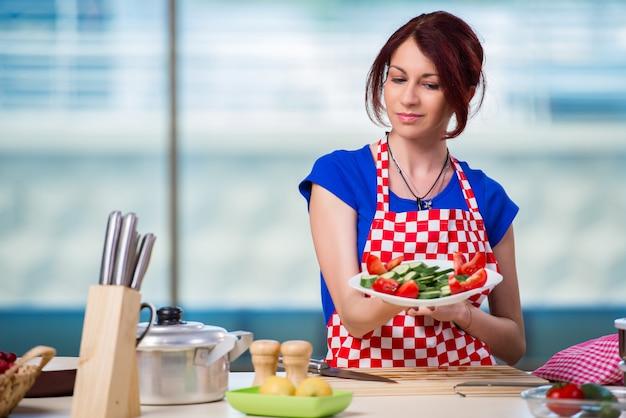 Mujer joven que trabaja en la cocina