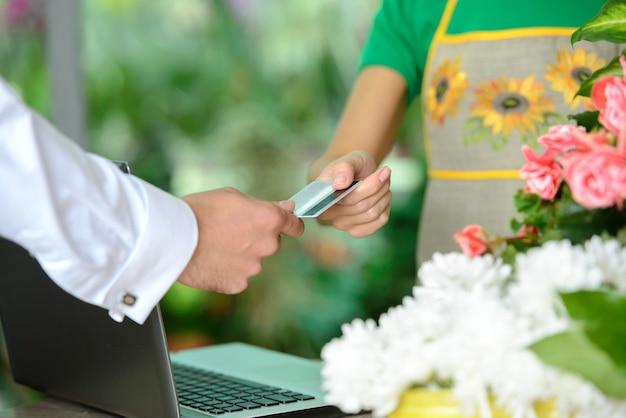 Mujer joven que trabaja como florista dando tarjeta de crédito.