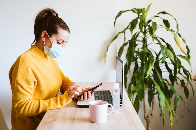Mujer joven que trabaja en la computadora portátil en casa, con máscara protectora. trabaja desde casa, mantente seguro durante el coronavirus covid-2019 concpt