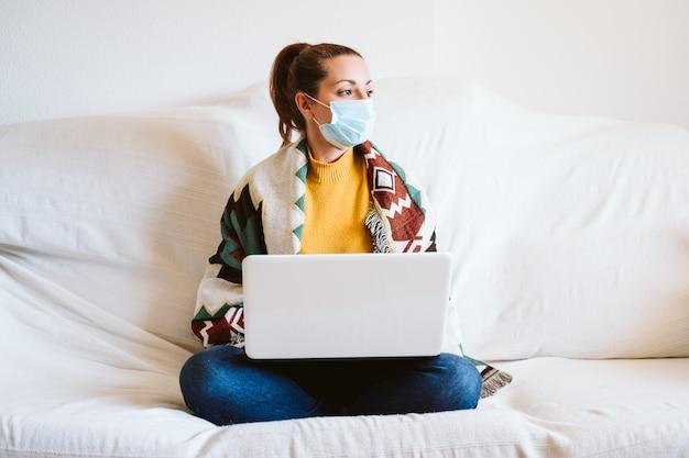 Mujer joven que trabaja en la computadora portátil en casa, sentado en el sofá, con máscara protectora. concepto de quedarse en casa durante el coronavirus covid-2019