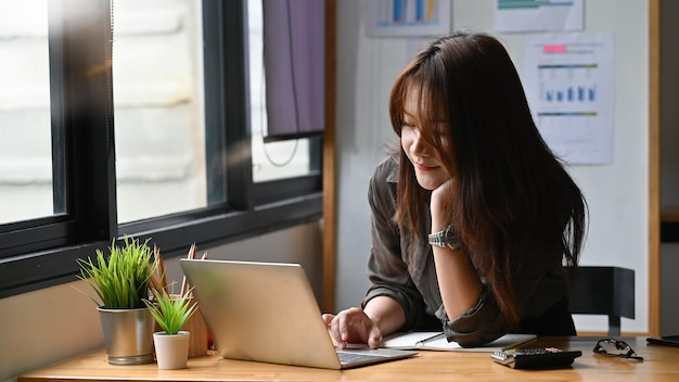 Mujer joven que trabaja con la computadora portátil en el espacio de la oficina moderna.