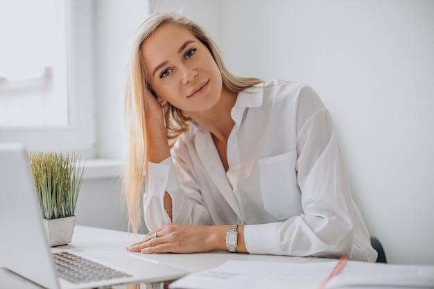 Mujer joven que trabaja en la computadora portátil en la oficina y mirando a la cámara